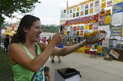 20140830bwShoreLocal07 Justine Bailey of Hoboken, N.J., and a native of Jefferson Hills, takes a photo of her ribs and corn bread Saturday at the Coors Light Kickoff and Rib Festival.