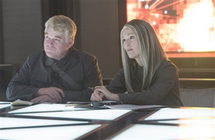 "HungerGames_preview Plutarch Heavensbee (the late Philip Seymour Hoffman) and President Coin (Julianne Moore) in ""The Hunger Games: Mockinjay - Part 1."""