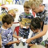 Kindergarten teacher Lindsay McKee, right, helps her new students get acquainted by asking them to match uppercase and lowercase letters at Cornell Schools' Kindergarten Boot Camp three weeks before school was to begin. The staff and students all wore camouflage shirts.
