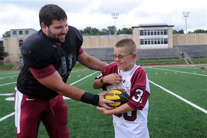 20140902JHSportsKitterman03-2 Carnegie Mellon senior defensive lineman Dustin Schneider hands off to Brock Kitterman, 9, from Bethel Park, who has been paired with the CMU football team as part of Team IMPACT. Kitterman, who has bilateral retinoblastoma, a very rare eye cancer, will be the team's captain this season.