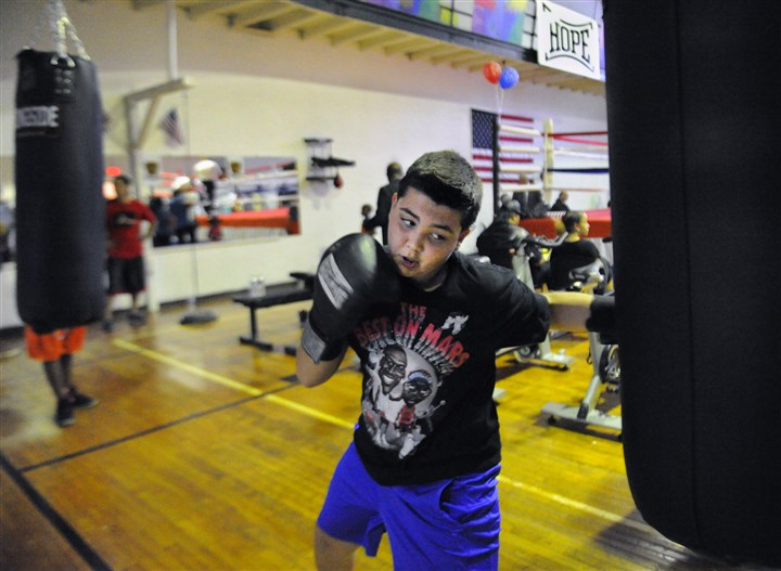 20140903JHLOCALBoxing02-1 Anthony Zigarella, 13, works the heavy bag during the dedication and ribbon-cutting ceremony Wednesday.
