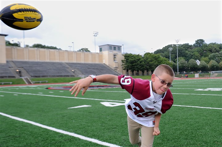 20140902JHSportsKitterman02-1 Brock Kitterman, 9, from Bethel Park, has been paired with the CMU football team as part of Team IMPACT. Kitterman, who has Bilateral Retinoblastoma, a very rare eye cancer, will be the team's captain this season.