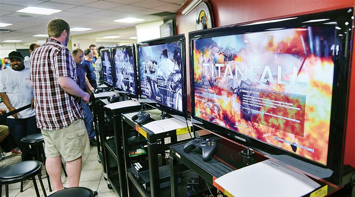 "20140903lrtitanfallgamingbiz02-5 Television screens are set up Wednesday at the Art Institute of Pittsburgh so that students, faculty and administration can participate in the ""Titanfall"" tournament. Two creators of the ""Titanfall"" game for Respawn Entertainment are Art Institute alumni."