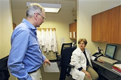 Nurses Doug Johnson, left and Sharon O'Dwyer work at the medical center of the AIDS Resource Center of Wisconsin in Milwaukee. The medical center will serve as a primary care center and service coordinator for people with HIV who are covered by Medicaid.