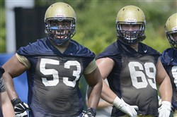 Offensive linemen Dorian Johnson (53) and Adam Bisnowaty (69) on the first day of Pitt preseason football practice last month at their training facility on the South Side.                     Original Filename: 20140804radPittPracticeSpts.21.jpg