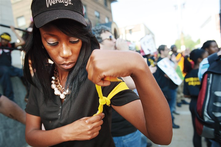 20140904jrStrikeLocal2-1 Ashona Osborne, 22, of Penn Hills, who works at Wendy's, ties a yellow ribbon around her arm during a fast food workers' protest today in Wilkinsburg. Ms. Osborne said the ribbon is a symbol of civil disobedience and that she planned to get arrested during the protest to draw attention to the problem of low wages.