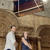 "Chilean artist Sebastian Errazuriz and Rachel Delphia, Carnegie Museum of Art curator of decorative arts and design, stand under his work ""The Piano,"" which hangs in the museum's Hall of Architecture. The exhibition is titled ""Sebastian Errazuriz: Look Again."""