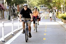 Bicyclists ride along bike lanes on Penn Avenue, Downtown.