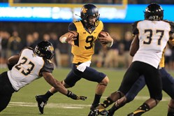 West Virginia quarterback Clint Trickett carries the ball during the first half of a game against Towson in Morgantown, W.Va., earlier this month.
