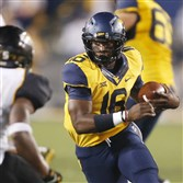 Mountaineers quarterback William Crest Jr. carries the ball against Towson cornerback Donnell Lewis in the third quarter Saturday at Milan Puskar Stadium in Morgantown, W.Va,