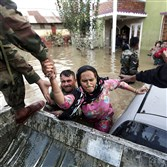 Indian army soldiers rescue a Kashmiri woman from her flooded house Wednesday in Srinagar. Flood waters started receding in Indian Kashmir, giving rescue teams a chance to reach tens of thousands of villagers stranded by the heaviest rainfall in half a century. Floods and landslides have killed at least 450 people in India and Pakistan and cut off more than 1 million people from basic services.