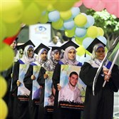 Palestinian graduates attend their graduation ceremony Wednesday as they hold posters of students who were killed in the seven-week Israeli offensive and were supposed to be among those graduating at the University College of Applied Sciences in Gaza City.