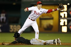 Pirates' Starling Marte steals second base as Phillies second baseman Chase Utley handles the throw from home during the third inning in Philadelphia.