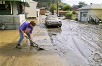Jann Berhardt shovels mud from the sidewalk in front of her Etna home during the aftermath of Hurricane Ivan in September 2004.