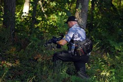 A Pennsylvania State Trooper walks into a wooded area Sunday across the street from the Blooming Grove barracks. Cpl. Byron Dickson was killed in a Friday night attack.