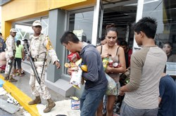 Mexican soldiers Monday try to stop people from looting a convenience store, which was destroyed by Hurricane Odile in Los Cabos, Mexico.