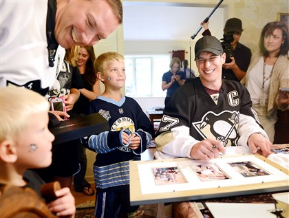 Pitts­burgh Pen­guins' Sid­ney Crosby jokes with the Bianchin fam­ily Mon­day while sign­ing au­to­graphs in their Frank­lin Park home. Reuben Bianchin stands with his kids Miles, 5, left, and Tyler, 7. Mr. Crosby de­livered tick­ets as part of an an­nual Pen­guins pro­mo­tion.