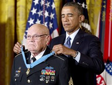 President Barack Obama bestows the Medal of Honor on retired Army Command Sgt. Maj. Bennie G. Adkins on Monday in the East Room of the White House in Washington.