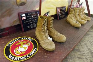 "Boots, plaques, dog tags and other memorabilia lay at the bottom of the large paintings in ""The Eyes of Freedom"" memorial at the Pittsburgh Technical Institute."