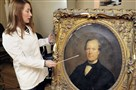 Conservator Rikke Foulke displays the various damage marks on an early portrait of Pittsburgh's first city controller, Henry Lambert, at Heinz History Center's new conservation center. This portrait of Mr. Lambert, by Albert Lauck Dalbey, was painted in 1865.