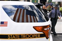 The U.S. flag is reflected in the window of a Pennsylvania State Police vehicle in Scranton for the viewing of Cpl. Bryon Dickson. Trooper Dickson was killed on Friday night in an ambush shooting at the state police barracks in Blooming Grove.