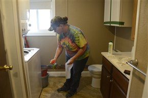Angela Rose of Rigmaids cleans the washer in the bathroom of one of the trailers at Stallion Oilfield Services.