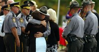 A woman embraces a Pennsylvania state trooper during the viewing of Pennsylvania State Trooper Cpl. Bryon Dickson Wednesday in Scranton.