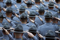 Law enforcement officers salute as the honor guard arrives for the funeral of Pennsylvania State Trooper Cpl. Bryon Dickson on Sept. 18.