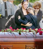 Tiffany Dickson embraces her 7-year-old son Bryon, in front of the casket of her husband, Pennsylvania State Trooper Cpl. Bryon Dickson, Thursday at Dunmore Cemetery in Dunmore in northeastern Pennsylvania.