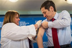 Dr. Thomas Frieden, Director of the Centers for Disease Control and Prevention, receives a flu shot from Sharon Bonadies at the conclusion of a press conference at the National Press Club in Washington, D.C. Thursday.
