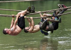 Racers at BattleFrog Tri-State hang on as they try to complete the rope traverse obstacle.