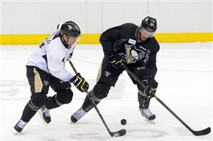 Tom Kostopoulos, left, battles for the puck with Philip Samuelsson in the Penguins training camp at Consol Energy Center.