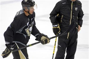 Sidney Crosby skates past new coach Mike Johnston in the Penguins training camp at Consol Energy Center.