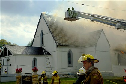 Firefighters try to put out the fire at St. Paul Baptist Church in Oakmont.