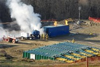Firefighters work at the site of a fire and spill in March 2010 at an Atlas Resources well site in Washington County. The fire, below, sent a large plume of smoke into the air.