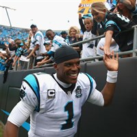 Cam Newton of the Carolina Panthers slaps hands with the fans after defeating the Detroit Lions 24-7 during the game at Bank of America Stadium on September 14, 2014 in Charlotte, North Carolina.