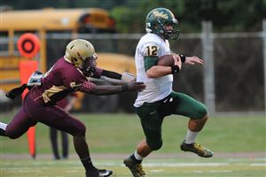 Seton-LaSalle quarterback Tyler Perone, is chased down by Steel Valley's Tyrone Freeman during the first quarter at the Steel Valley stadium in Munhall.