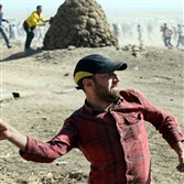 A man throws stones toward Turkish security forces who were using teargas and water cannons to disperse protesting local people as several hundred Syrian refugees waited, at the border in Suruc, Turkey, on Sunday.