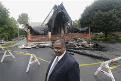 The Rev. Shane Austin of St. Paul Baptist Church outside the burned church before Sunday worship held at a community center across the street.