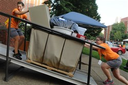 In this 2013 photo, Kait Miller, of Dublin, Ohio, and Elise Wilson, of Wilkins Township, get their speed up as they take a cart loaded with a student's belongings up a ramp leading to Vickroy Hall at Duquesne University.