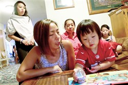 Sia Her, left, came to America when she was 4. Here she reads a book with her niece, Izzy Lee. Behind her are two other nieces, Maddy Lee, at left and Natalie Lee, right, on either side of Ms. Her's mother, Khou Yang.