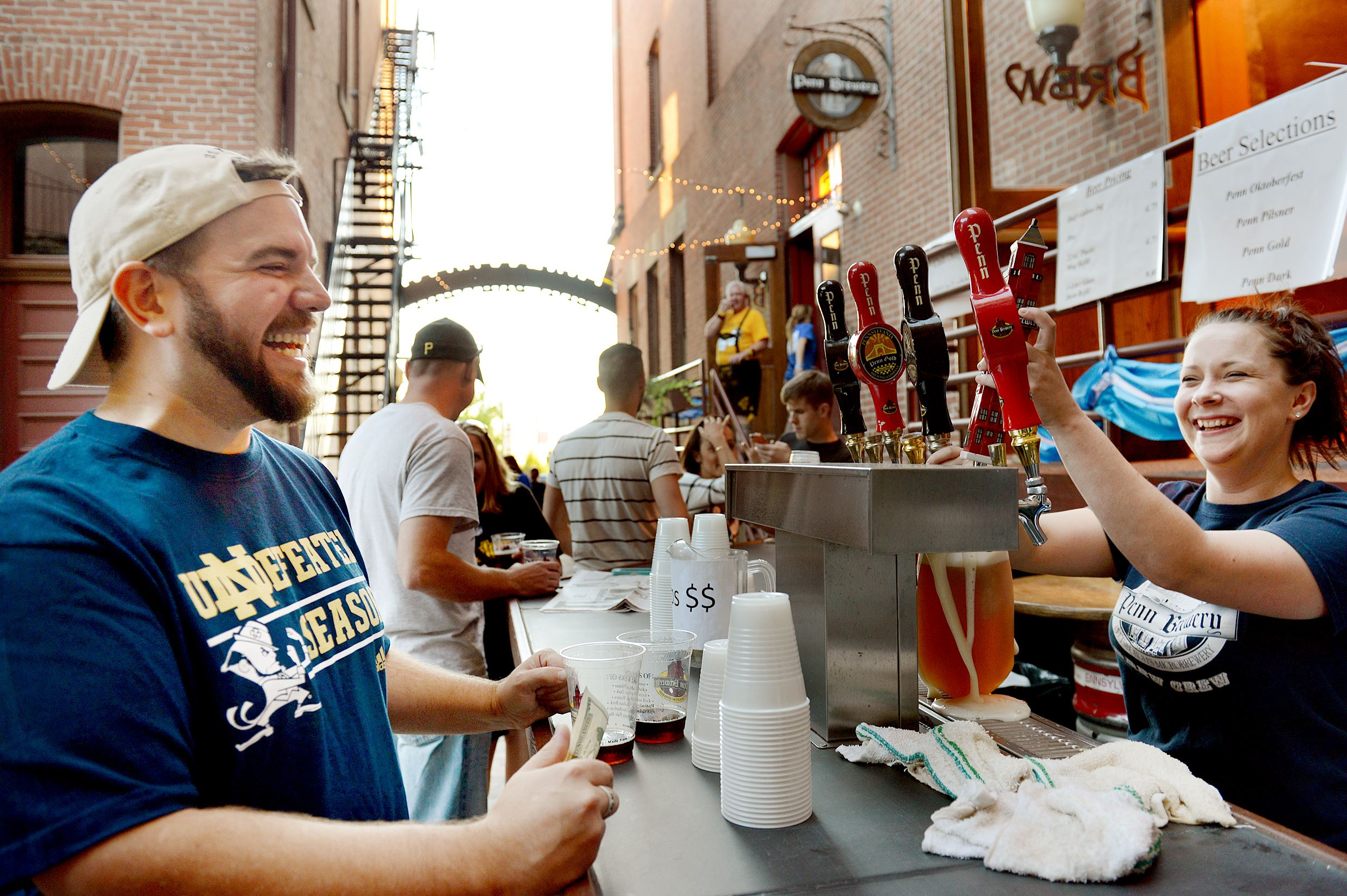 20140921jrOktoberfestMag1 Marie Kozak serves beer to Chris Miller of Esplen during Oktoberfest 2014 at Penn Brewery.