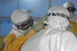Dr. Joel Montgomery, team leader for the U.S. Centers for Disease Control and Prevention Ebola Response Team in Liberia, is dressed in his personal protective equipment while adjusting a colleague's PPE before entering the Ebola treatment unit in Monrovia, Liberia's capital city in this photo released Sept. 16.