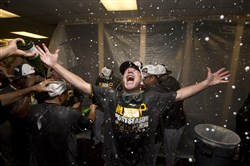 Pirates coach Rick Sofield celebrates in the locker room after the Pirates defeated the Atlanta Braves 3-2 in a baseball game to clinch a playoff berth, Tuesday, Sept. 23, 2014, in Atlanta.