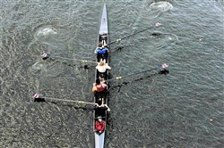 A crew team rows downstream along the Allegheny River near the 16th Street Bridge.