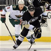 The Penguins' Jayson Megna moves the puck up ice against the Wild's Mikko Koivu in September.