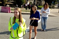 Maddie Manning of the Oakland Transportation Management Association leads Sara Klein, a Pitt senior, and Nicole Barnett of the Allegheny County Health Department across Forbes Avenue in Oakland during a pedestrian safety event on Monday.