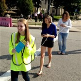 Maddie Manning of the Oakland Transportation Management Association leads Sara Klein, a Pitt senior, and Nicole Barnett of the Allegheny County Health Department across Forbes Avenue in Oakland during a pedestrian safety event Monday.