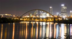 A night view of the Birmingham Bridge with part of the Pittsburgh skyline.