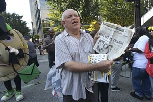 "A baseball fan Downtown who says his name is ""Ed"" displays a copy of the Post-Gazette from 1960, when the Pirates beat the Yankees on Bill Mazeroski's home run."